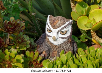 Owl statue sitting between the flowers in the garden