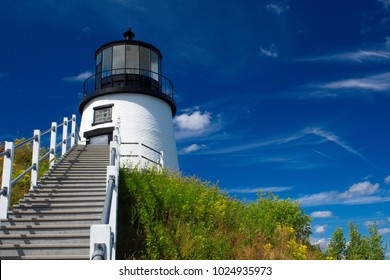 Owls Head Lighthouse on a sunny summer day with bright blue sky