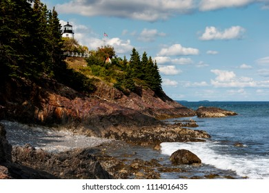 Owls Head lighthouse over rocky cliffs overlooking harbor at low tide in Maine.