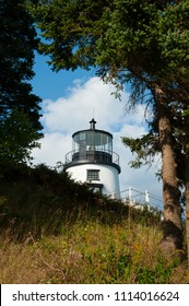 Owls Head lighthouse, with its rare fresnel lens, sits on a hilltop by evergreen trees on a summer day in Maine.