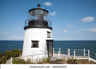 Owls Head lighthouse sits atop a 100 foot cliff over the ocean below, on a summer day in Maine.