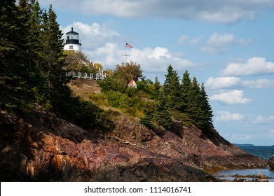 Owls Head lighthouse sits atop rocky cliffs overlooking Rockland Harbor on a summer day in Maine.