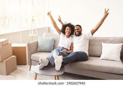 Own House. Joyful Black Spouses Celebrating Real Estate Purchase And Moving To New Home Sitting Among Unpacked Boxes Indoor After Relocation, Smiling To Camera. Apartment Ownership Concept