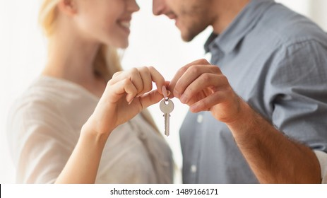 Own House. Spouses Holding New Apartment Key Hugging Looking At Each Other Indoor. Panorama With Empty Space, Cropped, Shallow Depth