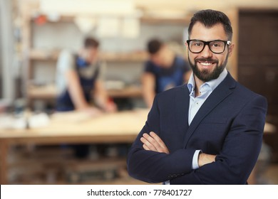 Owner of business and staff in carpentry workshop