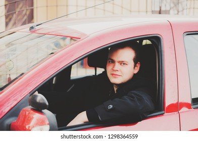 The owner of the car is a young man and a new red car on the street.