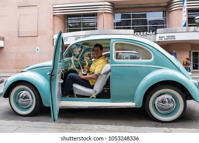 Owner of classic pale blue Volkswagen Beetle sitting in his car proudly holding golden trophy during vintage car competition, St. Denis Street, Montreal, Quebec, Canada, May 7, 2016