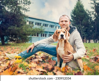 Owner with his dog on the autumn walk in park