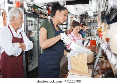 Owner Looking At Workers Cutting Cheese At Counter