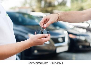 Der Besitzer eines neuen Autos, der die Schlüssel aus den Händen des Autohändlers holt
