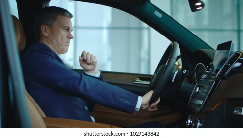 Owner of new car in showroom adult man sitting inside and smile.