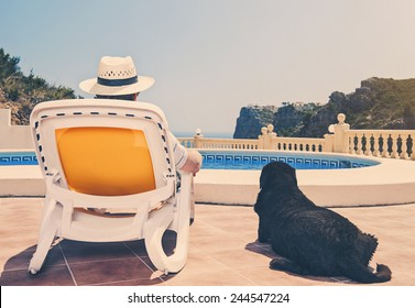 Owner relaxing by pool with dog beside him