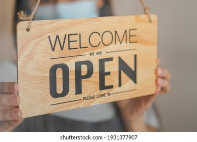 Owner retail,coffee shop woman turning sign board to open with wearing face mask ,protection to pandemic of coronavirus reopen store,restaurant after close lockdown quarantine in covid to new normal.