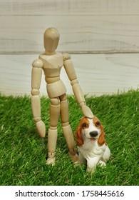 Der Besitzer zeigt dem Hund Liebe. Menschen- und Hundemodelle einzeln auf grauem Hintergrund. Der Besitzer liebt