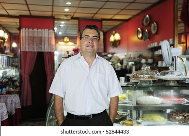 owner of a small business/ cake store/ cafe showing her tasty cakes