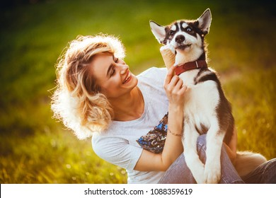 owner is smiling and feeding her dog by ice cream on the meadow in the park