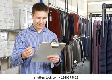 Owner Of Start Up Fashion Business In Warehouse With Clipboard