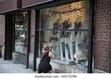 owner of store closing gate over window display with mannequins behind glass - woman with hat pulling down fence