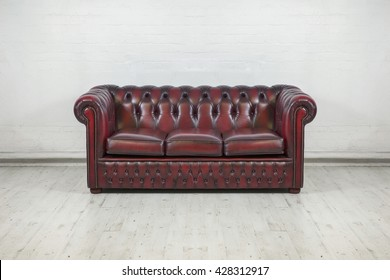 oxblood red vintage sofa against painted white brick wall