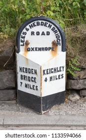 OXENHOPE, WEST YORKSHIRE UK JUNE 23 2018. An old West Riding road milestone showing distances to Hebden Bridge and Keighley
