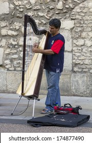 Oxford, England - July 10, 2010: A street musician plays the harp in Broad Street on July 10, 2010.
