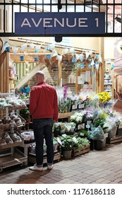 OXFORD, ENGLAND - JUNE 24, 2018: A customer at a flower shop in the Covered Market in High Street, Oxford. The Covered Market is a historic market opened on 1 Nov 1774 and is still active today.