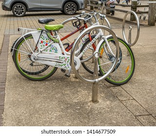 Oxford, England UK 05/31/2019 Pretty white and green Electra bike locked up at a large round metal bike parking stand next to a red Raleigh bike. Silver/grey car in background. People can be seen.