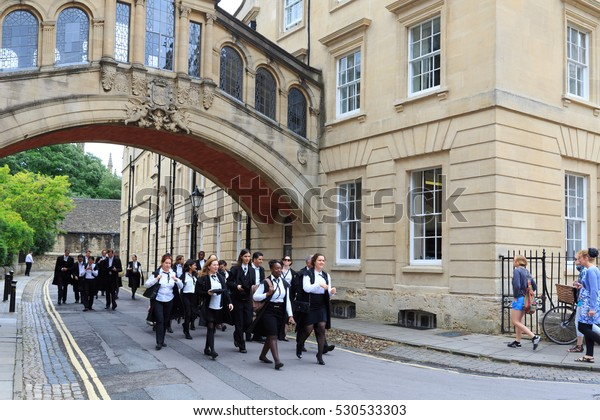 OXFORD - JUL 11, 2014 : Graduates of Oxford University walk by Hertford College, wearing traditional academic gowns.