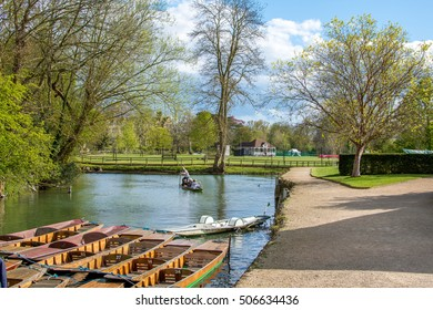 Oxford, UK - 30 April 2016: Tourists punting in river Cherwell on a sunny day near university of Oxford botanic gardens and  Magdalen Bridge