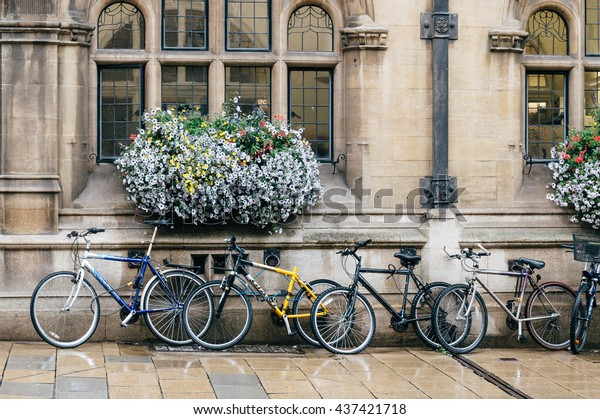 Oxford, UK - August 12, 2015: Bicycles parked in front of a building decorated with flowers. The city is known as the home of the University of Oxford.