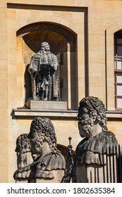 Oxford, UK - August 20th 2020: Statue of Edward Hyde, 1st Earl of Clarendon, on The Clarendon Building in Oxford, UK. The Heritage Heads sculptures of the Sheldonian Theatre are in the foreground.