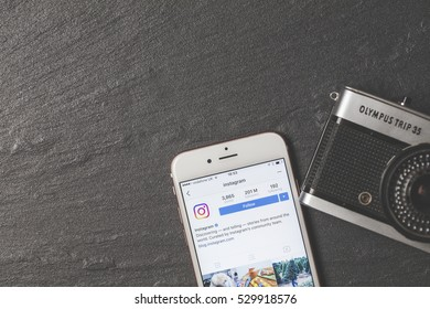OXFORD, UK - DECEMBER 5th 2016: An apple iPhone showing the instagram application alongside a vintage film camera.. Instagram is a popular social media application for sharing images and videos