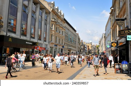 OXFORD, UK - JULY 9, 2014: Tourists walk along high street in central Oxford, England.