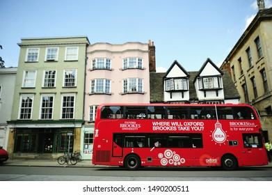 OXFORD, UK-29 JULY 2019: Red double deck bus of Brookes university stopping on the road in front of green and pink vintage buildings and Tudor house in Oxford, England, UK