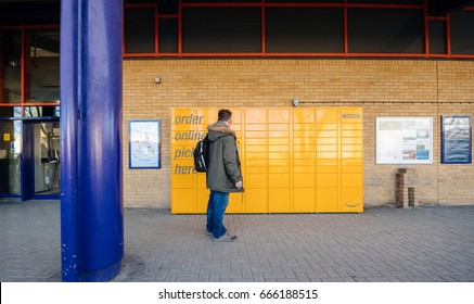 OXFORD, UNITED KINGDOM - MAR 2, 2017: Man looking at the Amazon locker orange delivery package locker train station - Amazon Locker is a self-service parcel delivery service
