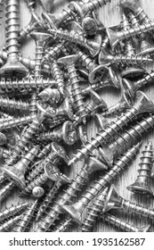 Oxidised screws, chrome-plated screws, brass-plated screws, a pile of assortment for domestic work. Black and white photo.