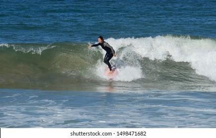 Oxnard, CA, U.S.A. 09/07/2019. Female surfer on the Hollywood Beach.