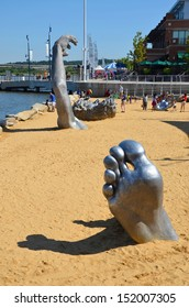 OXON HILL, MD - AUGUST 24: Awakening Sculpture at National Harbor on August 24, 2013 at Oxon Hill, MD USA. A famous 70-foot statue of a giant embedded in the earth created by J. Seward Johnson Jr.