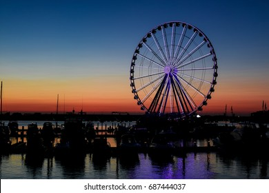 Oxon Hill, MD - July 30, 2017: The sun sets behind the Ferris wheel at National Harbor.