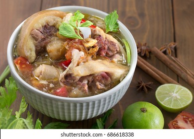 Oxtail soup, halal food, delicious, Muslim food in green bowl on dark brown wooden plate / Selective focus