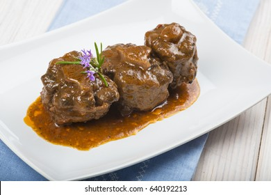 Oxtail stew served with its sauce and decorated with rosemary flowers