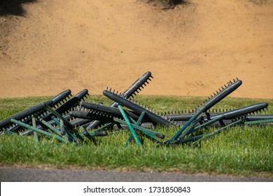 Oxted, UK - May 13 2020 - Sand brooms waiting to be put in a bunker on a golf course