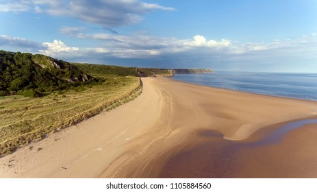 Oxwich Bay on the Gower peninsula in Swansea, UK, a long sweeping sandy bay with a shallow water line with easy access by road from Swansea attracts visitors from all over the UK