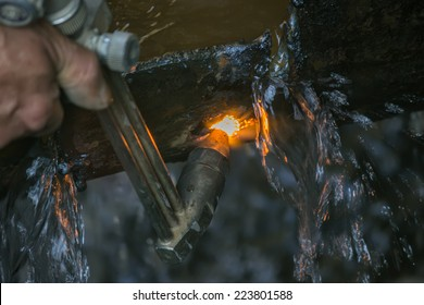 Oxy Acetylene torch. Cutting torch is used to cut a steel pipe with water. Selective focus.