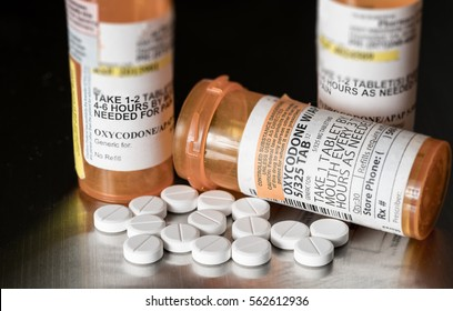 Oxycodone is the generic name for a range of opoid pain killing tablets. Prescription bottle for Oxycodone tablets and pills on metal table for opioid epidemic illustration