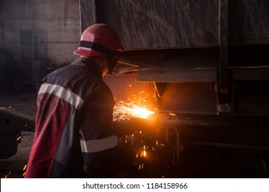the oxygen cutting operator cuts the worn out part from the railroad freight car.