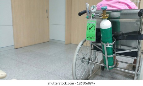 Oxygen cylinder for patient on wheelchair, and Thai words are available. At hospital.