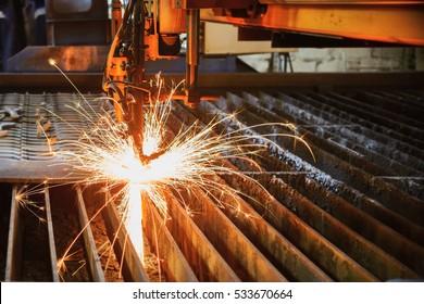 Oxygen torch cuts steel sheet. CNC gas cutting machine. Bright sheaf of sparks of molten metal