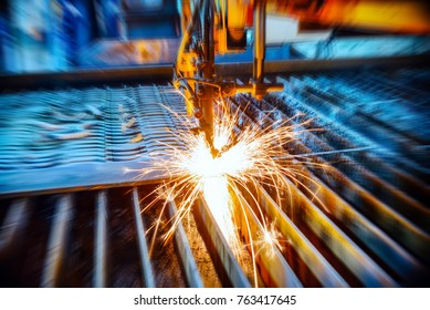 Oxygen torch cuts steel sheet. CNC gas cutting machine. Abstract industrial background, motion blur effect.