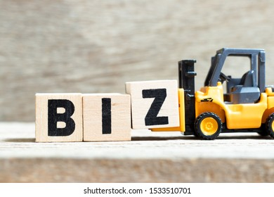 oy forklift hold letter block Z to complete word biz (Abbreviation of business) on wood background